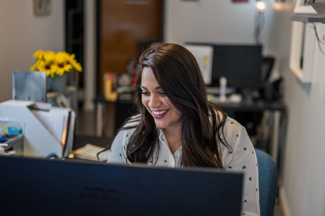 Female recruiter smiling and looking at computer screen with yellow flowers in background