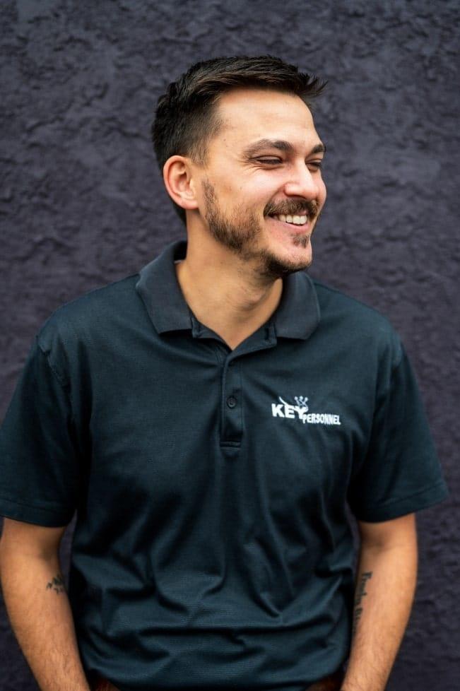 El director de proyectos y desarrollador de sitios web de KP Staffing, Philip Cron, se ríe frente a un muro morado.