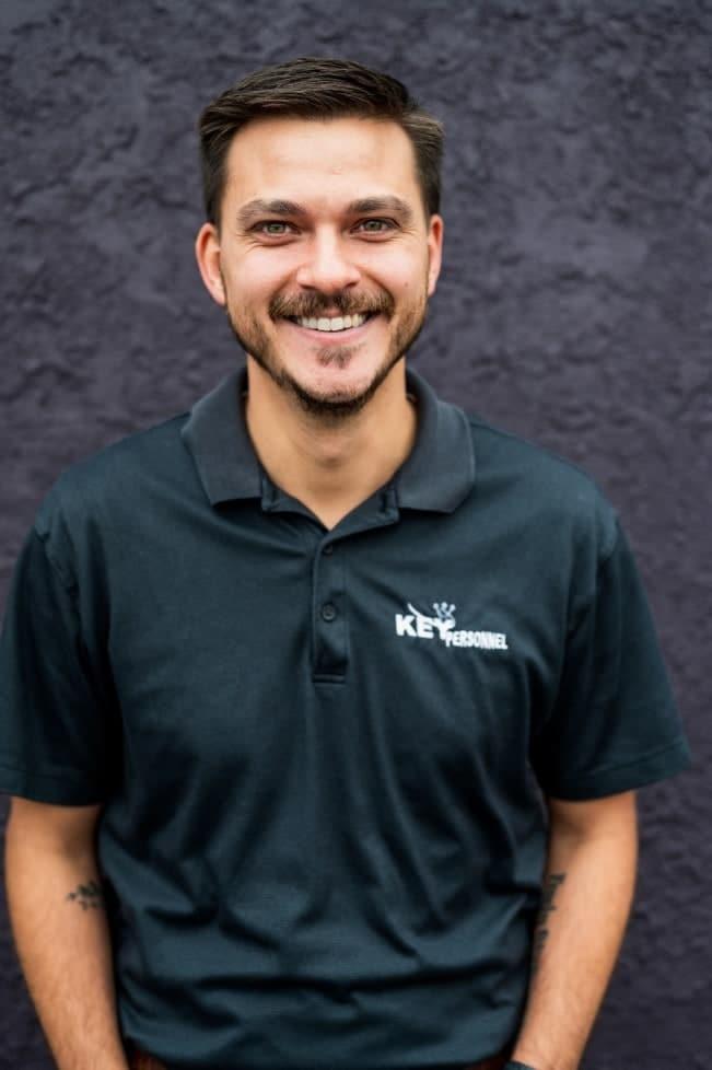 El director de proyectos y desarrollador de sitios web de KP Staffing, Philip Cron, sonríe frente a un muro morado.