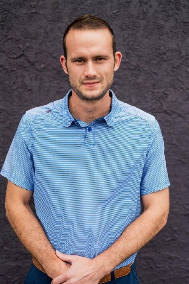 El director general de KP Staffing, Nathan Doran, sonríe suavemente frente a un muro de color púrpura.