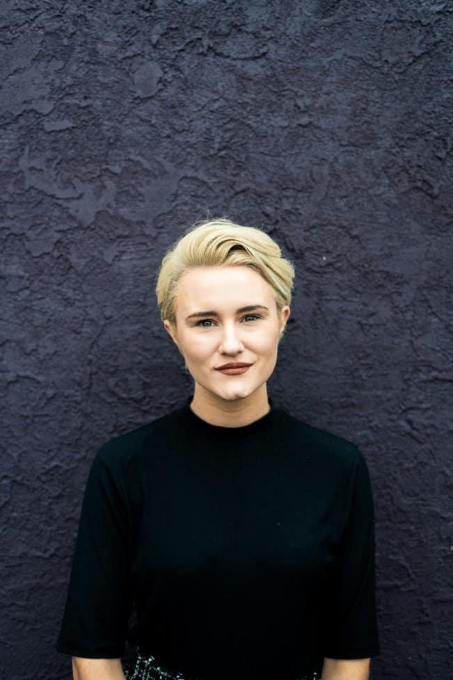 La jefa de marketing de KP Staffing, Christine Doran, sonríe suavemente frente a una pared de color púrpura.