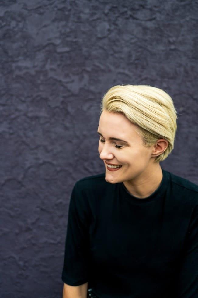 La jefa de marketing de KP Staffing, Christine Doran, se ríe frente a un muro morado.