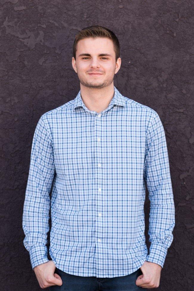 El director de AP/AR de KP Staffing, Luke Doran, sonríe suavemente mientras está de pie frente a una pared púrpura.