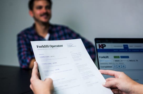 """A recruiter's hands hold a blurred resume, with the words """"Forklift Operator"""" clearly displayed at the top, and a blurred man in a flannel shirt sits on across the desk while being interviewed for the position."""
