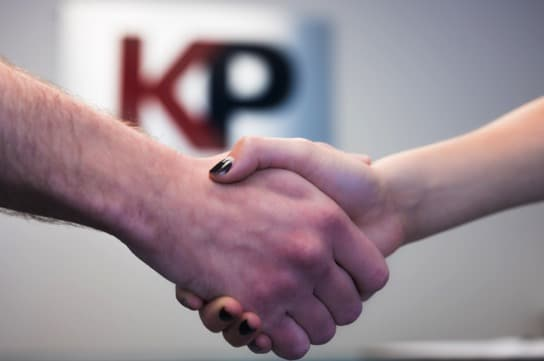 A man and woman shake hands in a brightly-lit room, with the KP Staffing logo blurred on the wall behind.