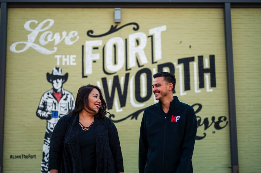 """KP Staffing employees smile and walk in front of the """"Love the Fort Worth the Love"""" mural on the side of Brewed Coffee, off Magnolia Street in Fort Worth, Texas."""